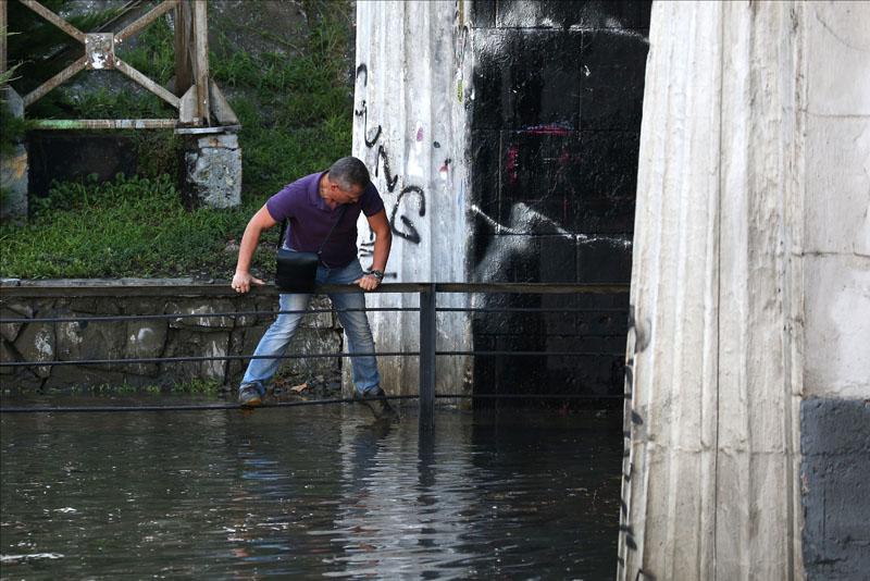 Мужчина на подтопленной после мощного ливня улице