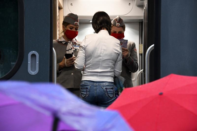 Проводницы проверяют билет у пассажирки поезда