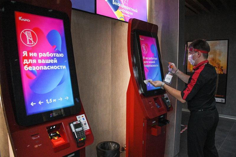 Сотрудник кинотеатра дезинфицирует автомат по продаже билетов