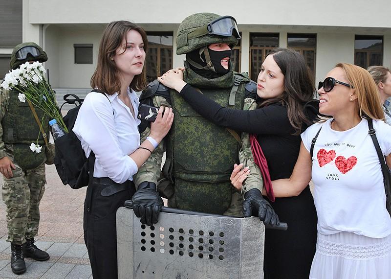 Участницы акции протеста и военнослужащий в Минске