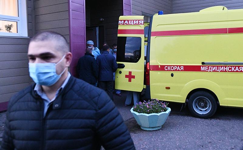 Медицинские работники загружают политика Алексея Навального в автомобиль скорой помощи