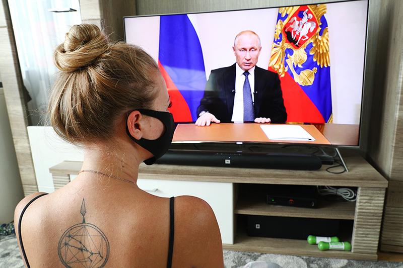 Девушка смотрит трансляцию обращения президента России Владимира Путина