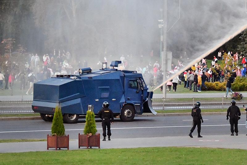 Автомобиль полиции поливает водой участников акции протеста оппозиции в Минске