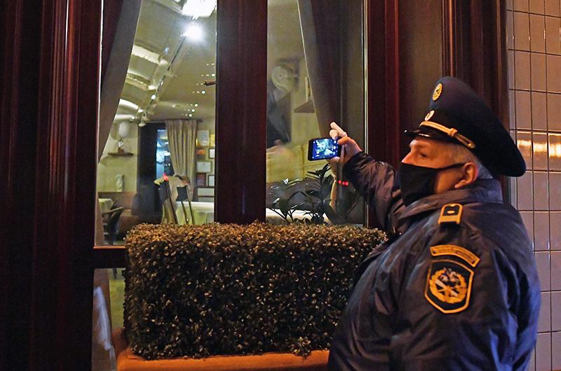 Сотрудник административно-технической инспекции возле входа в закрытый ресторан на одной из улиц в Москве