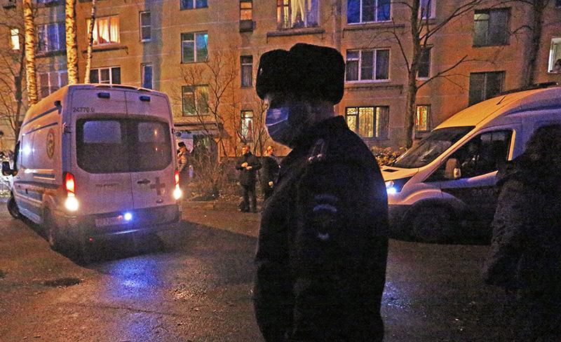 Сотрудник полиции у жилого дома, где мужчина держит в заложниках детей в квартиреу