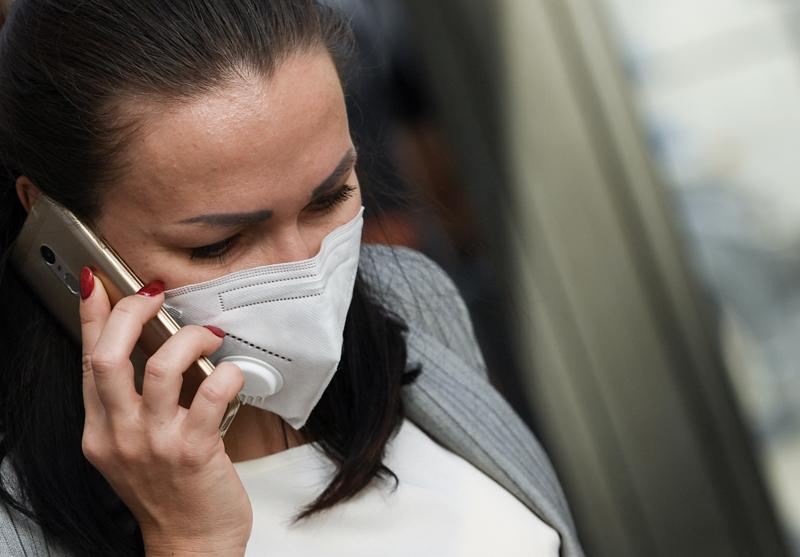 Девушка в защитной маске говорит по телефону
