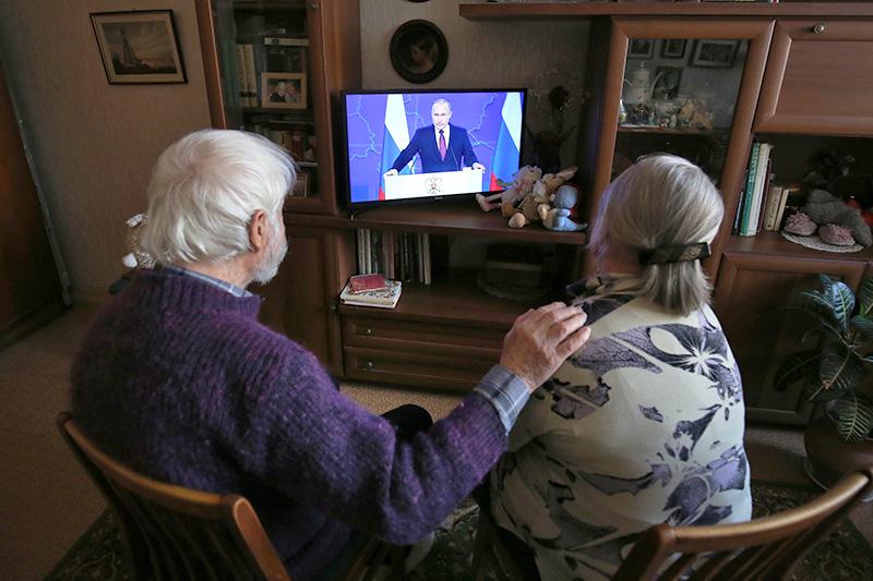 Люди смотрят телетрансляцию Владимира Путина