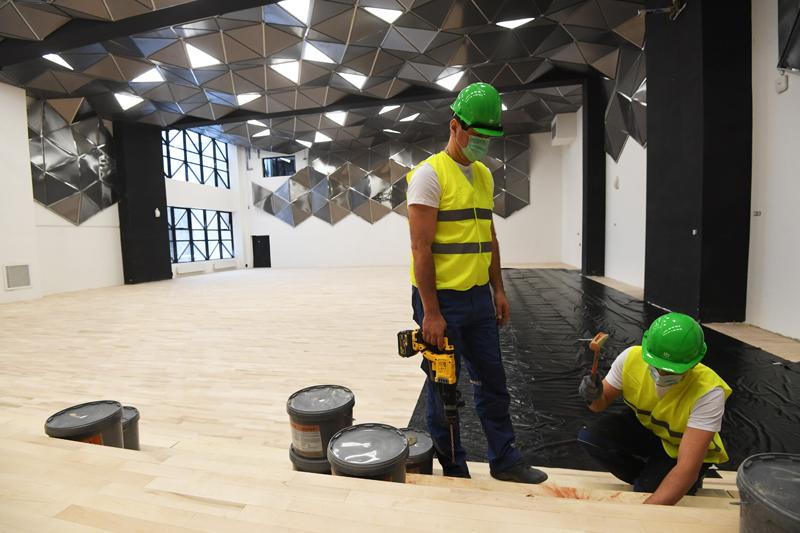 Строители в актовом зале в строящейся школе