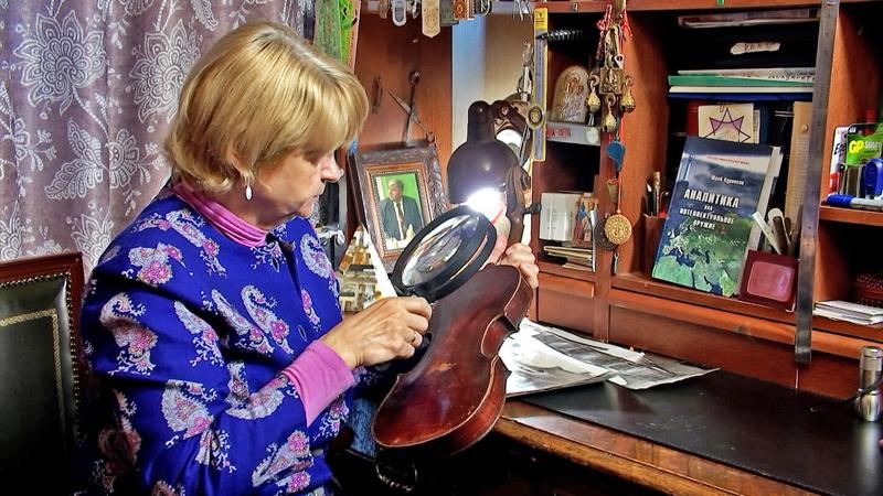 Эксперт осматривает скрипку