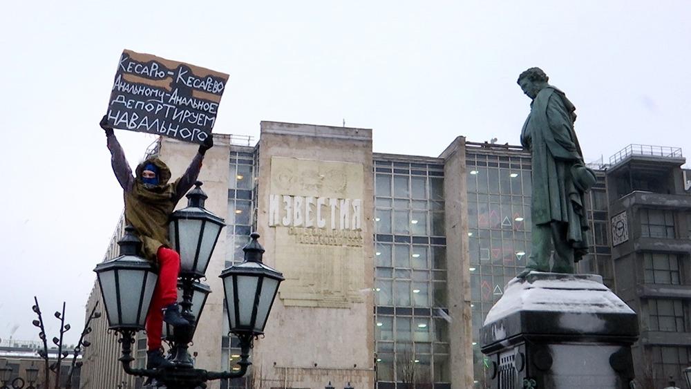 Участник несанкционированной акции с плакатом против Алексея Навального