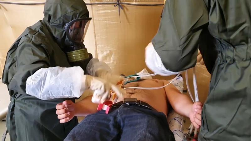 Военные медики обследуют пациента в полевом госпитале