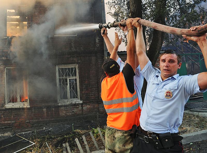 Сотрудник полиции тушит пожар