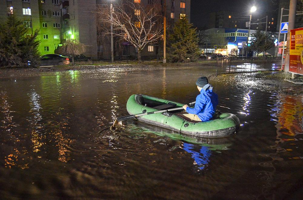 Жители Таганрога переплывают лужу на надувной лодке