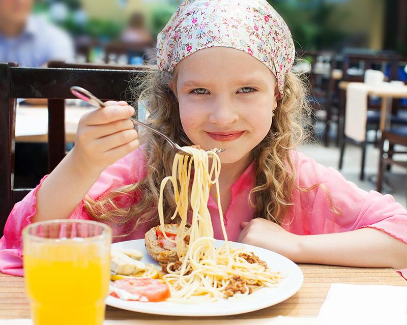 Девочка ест спагетти
