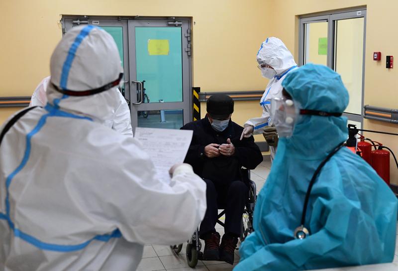 Врачи работают с пациентом в приемном отделении госпиталя для больных коронавирусной инфекцией COVID-19