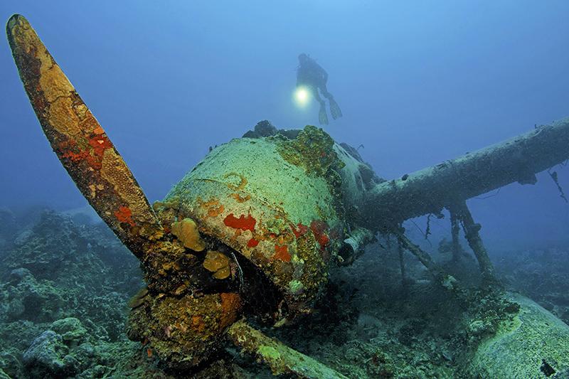 Дайвер обследует затонувший самолет