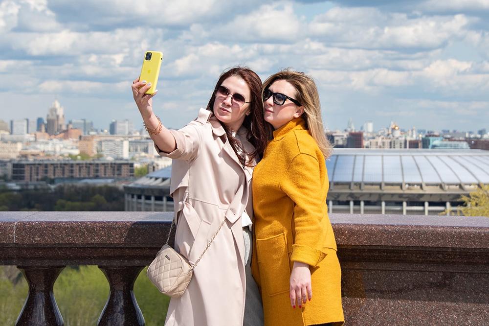 Люди делают селфи на фоне Москвы