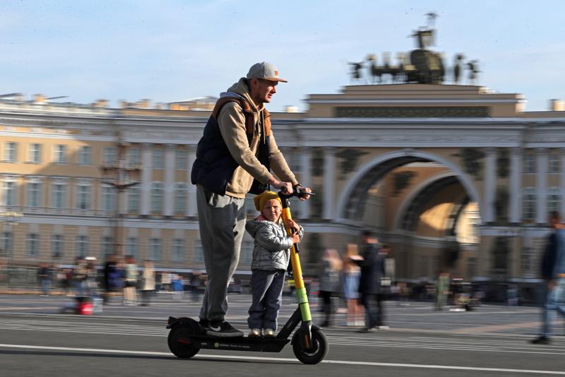 Мужчина и ребенок на электросамокате во время езды