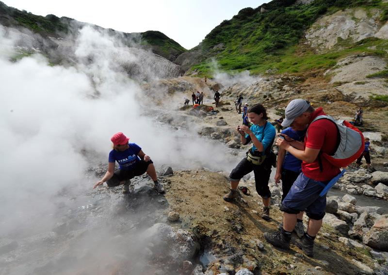 Туристы фотографируют друг друга в долине гейзеров