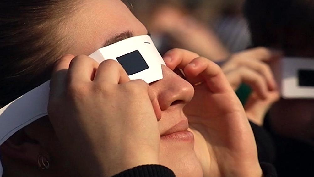 Люди наблюдают за Солнечным затмением