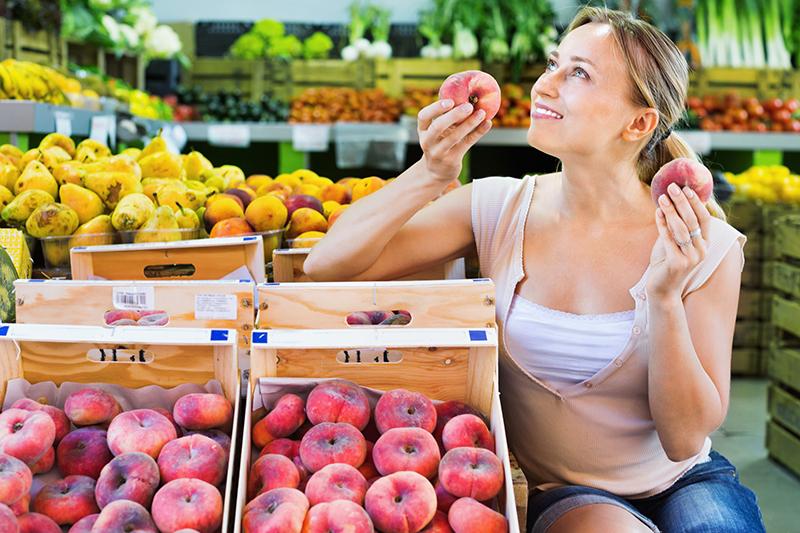 Девушка покупает персики