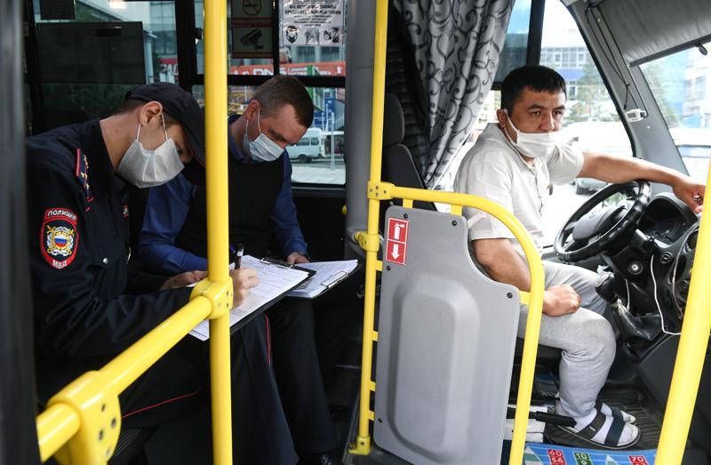 Сотрудники полиции оформляют протокол за нарушение масочного режима водителю маршрутного такси