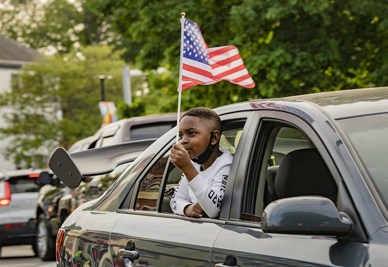 Молодой демонстрант держит американский флаг