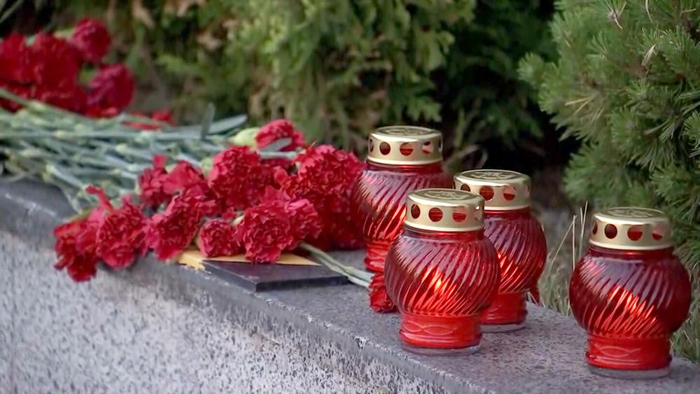 Цветы и свечи у мемориала Герою Советского Союза Цезарю Куников