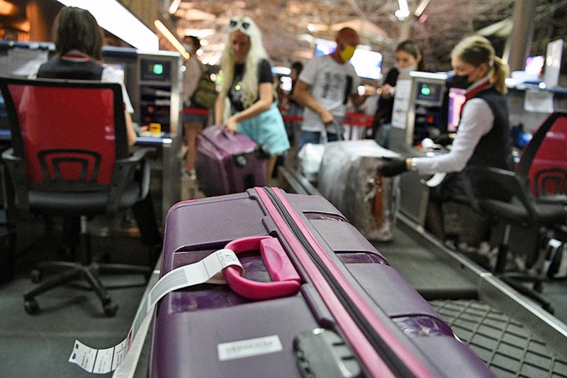 Пассажиры сдают багаж в аэропорту