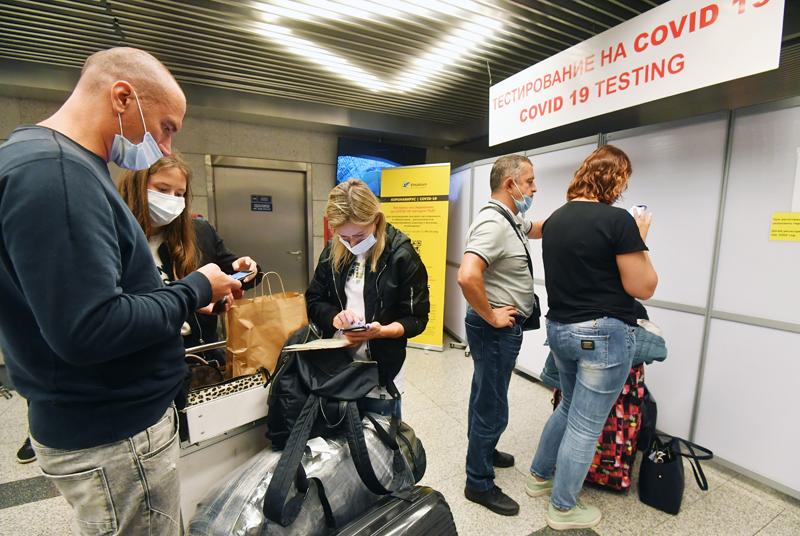 Пассажиры стоят в очереди на экспресс-тестирование на COVID-19