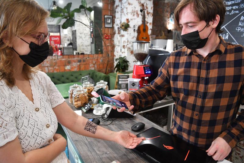 Сотрудник кафе сканирует временную татуировка с QR-кодом девушки в Москве