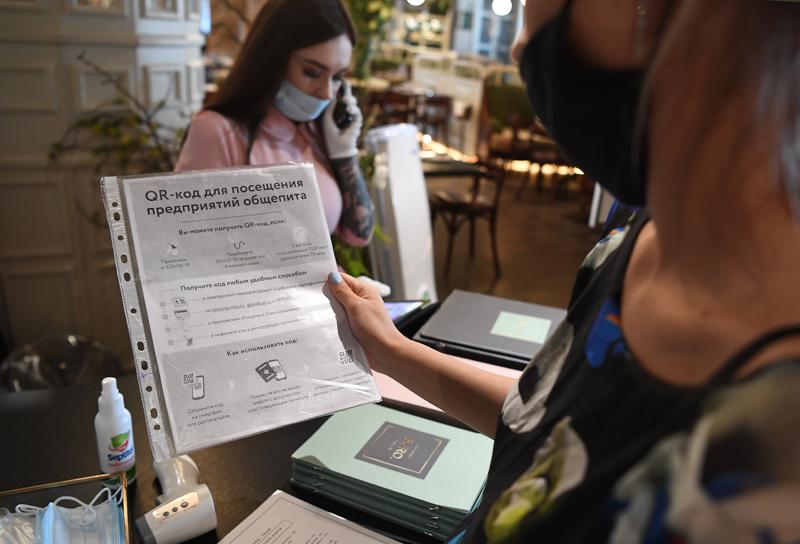 Посетительница изучает информацию о использовании QR-кода в ресторане