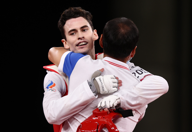 Михаил Артамонов (на втором плане) и тренер Илья Пак (ОКР) после победы