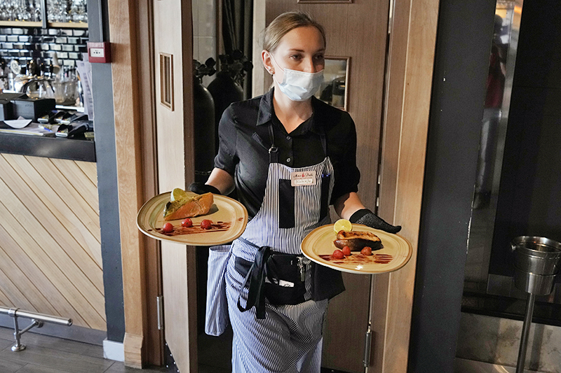 Официантка ресторана в медицинской маске