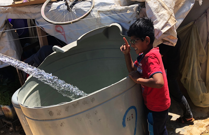 Мальчик набирает воду в бак в Сирии