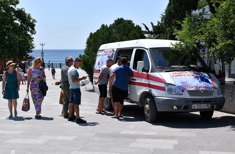 Люди около мобильного пункта вакцинации от COVID-19 на набережной Судака