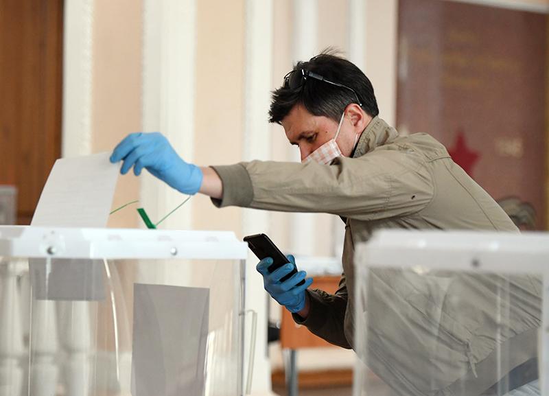 Мужчина фотографирует бюллетень во время голосования
