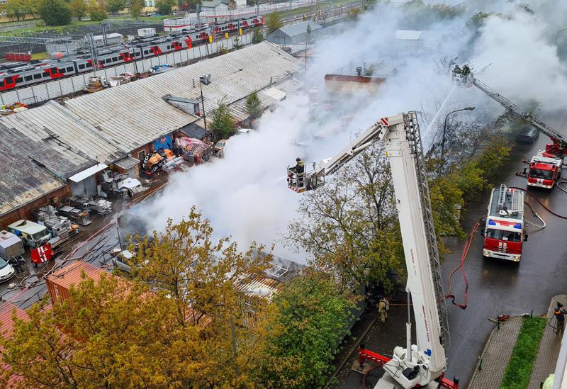 Работа пожарно-спасательных подразделений на месте возгорания в металлическом ангаре на территории промзоны