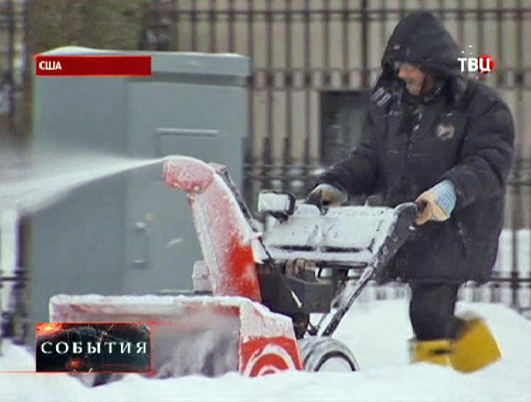 Мужчина чистит дорогу от снега