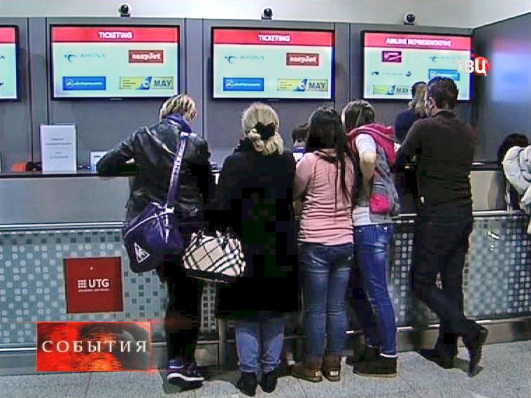Авиапассажиры стоят у стойки информации