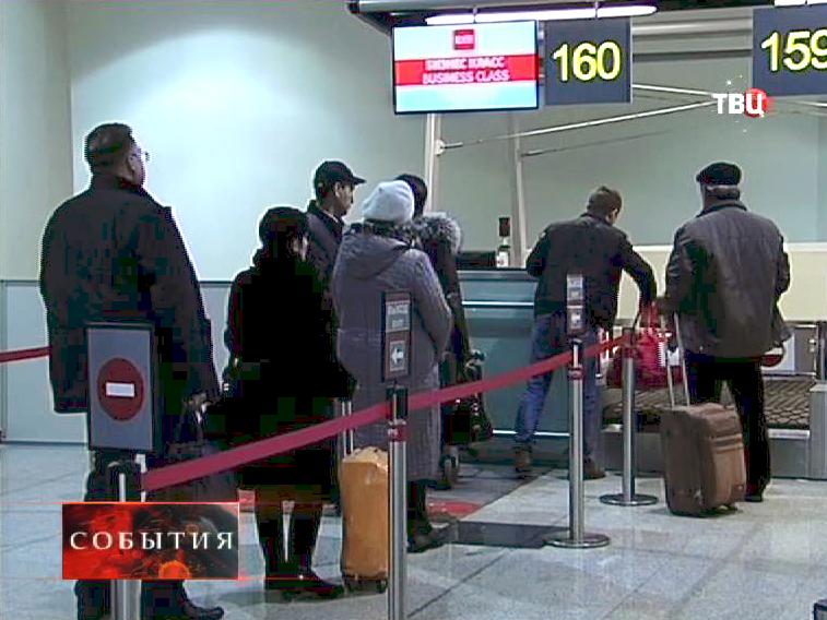 Пассажиры сдают багаж на стойке регистрации в аэропорте