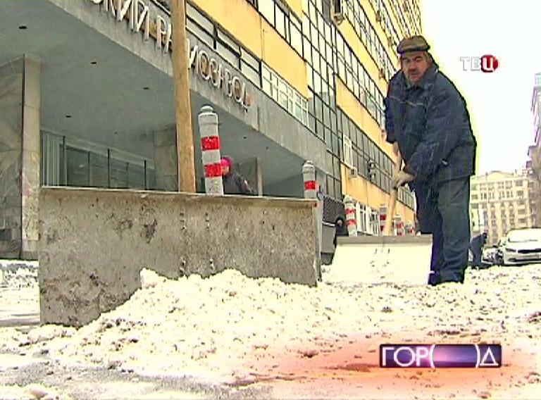 Дворник чистит тротуар от снега