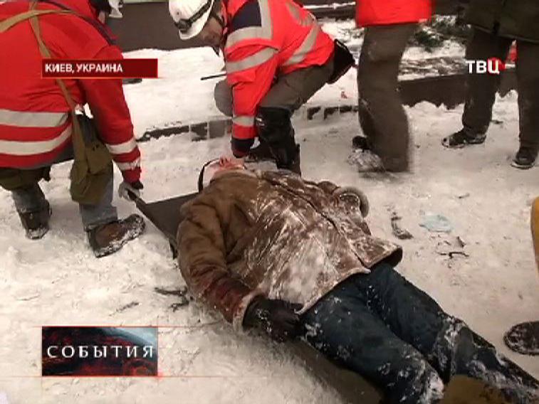 Врачи эвакуируют пострадавшего в беспорядках в Киеве