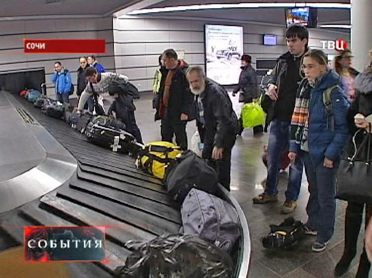 Пассажиры получают багаж в аэропорту