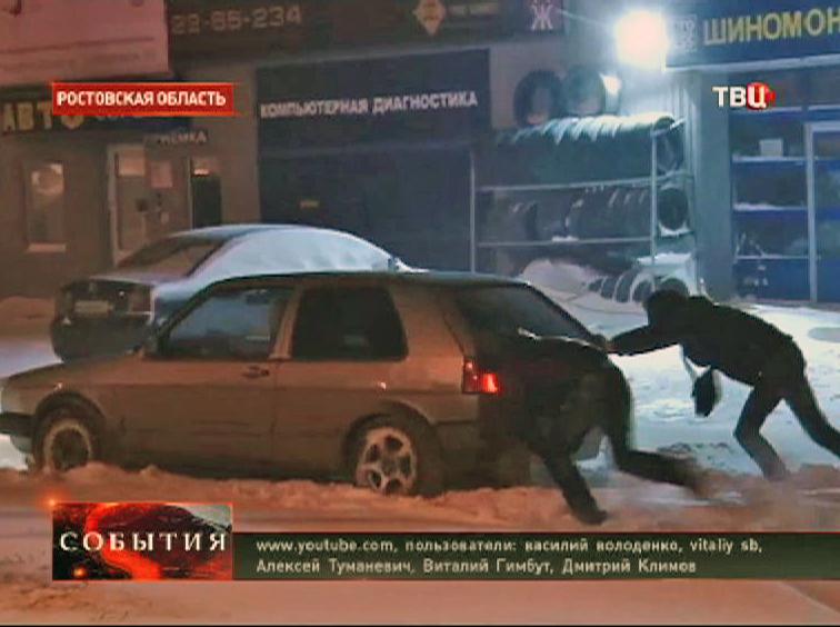 Автовладельцы вытаскивают машину из сугроба