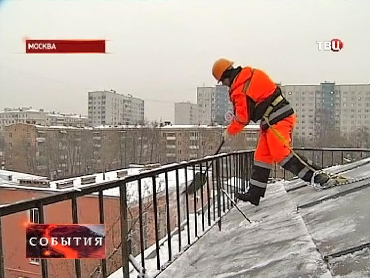 Дворники чистят крыши домов от снега