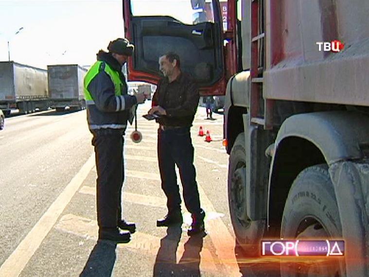 Инспектор ДПС проверяет документы водителя грузовика