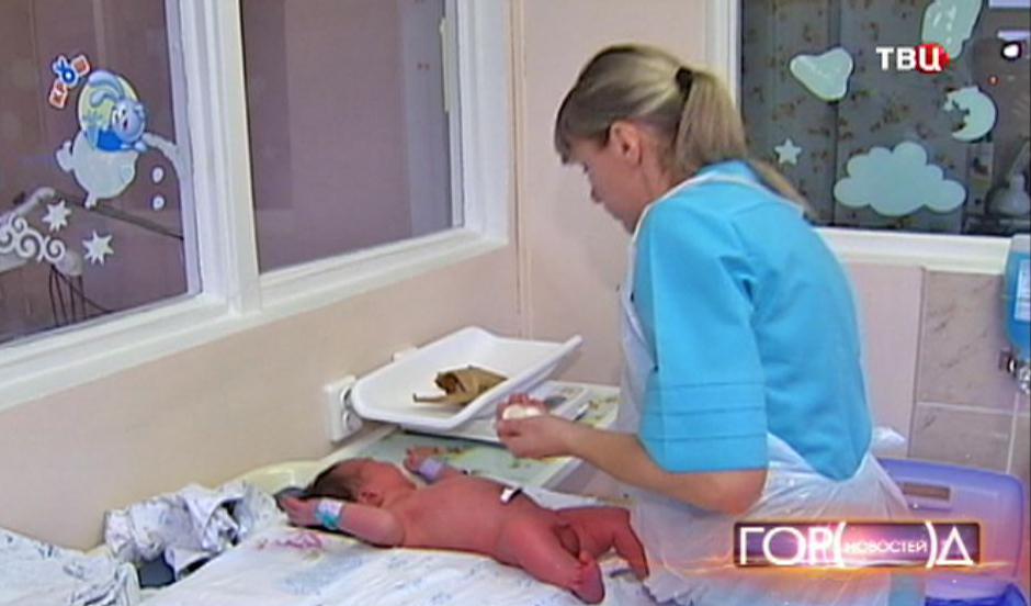 Акушер осматривает младенца