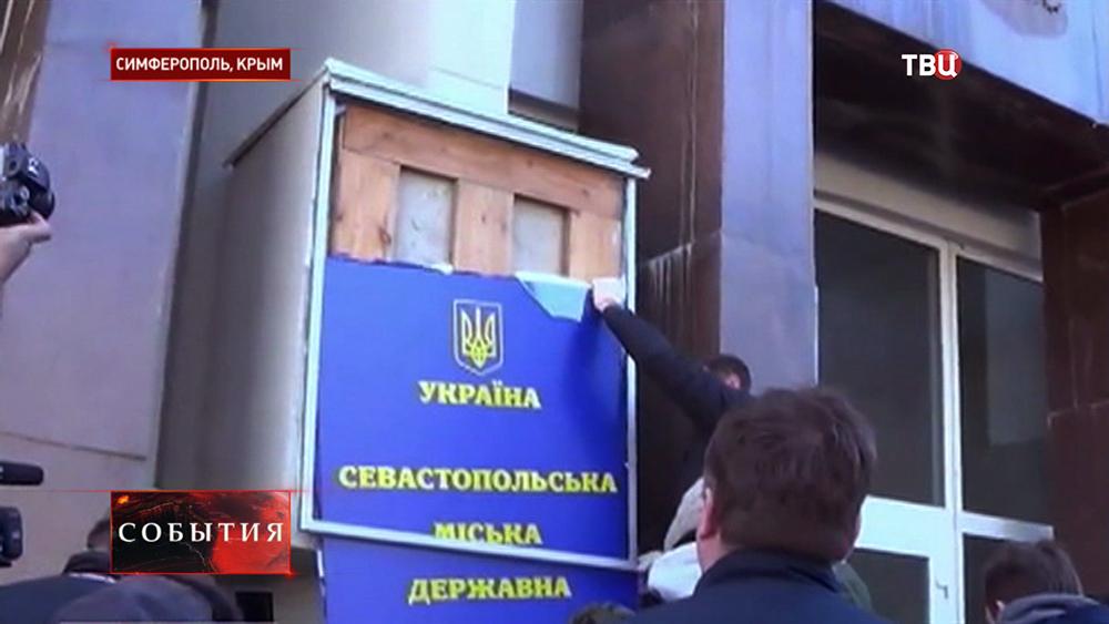 Демонтаж украинской таблички с административного здания в Симферополе