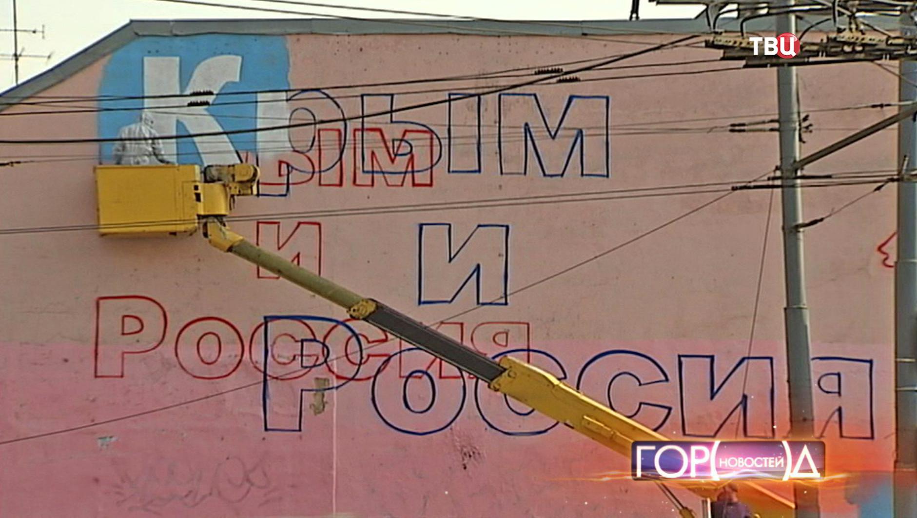 Художник рисует плакат на одном из домов
